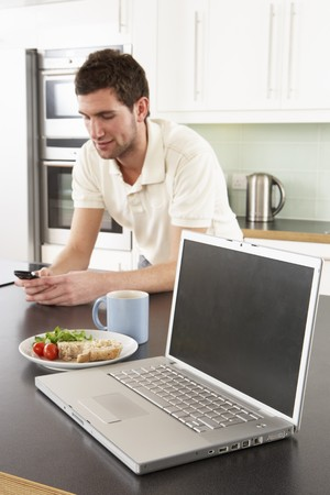 Young Man With Laptop In Modern Kitchen About To Eat Meal photo