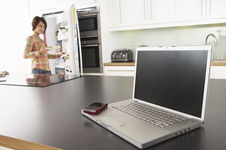 Young Woman Fixing Snack In Kitchen With Laptop In Modern Kitchen Stock Photo - 8453110