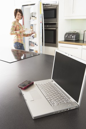 Young Woman Fixing Snack In Kitchen With Laptop In Modern Kitchen Stock Photo - 8453020