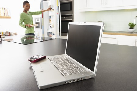 Young Woman Fixing Snack In Kitchen With Laptop In Modern Kitchen Stock Photo - 8453068