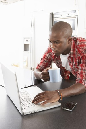 Young Man Using Laptop In Modern Kitchen photo