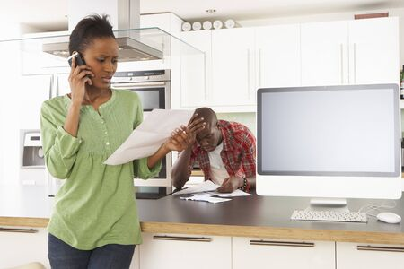 Young Couple Discussing Personal Finances In Modern Kitchen Stock Photo - 8452992