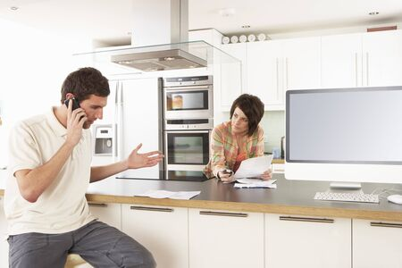 Young Couple Discussing Personal Finances In Modern Kitchen photo