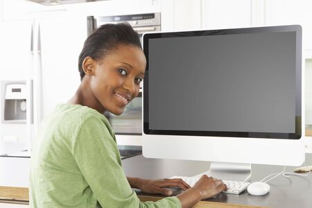 Young Woman Using Computer In Modern Kitchen