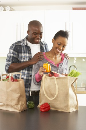 Young Couple Unpacking Shopping In Modern Kitchen photo
