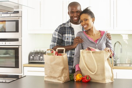 designer bag: Young Couple Unpacking Shopping In Modern Kitchen Stock Photo