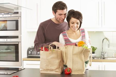 designer bag: Joven pareja desempaque de compras en la cocina moderna