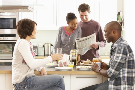multi racial groups: Group Of Young Friends Preparing Breakfast In Modern Kitchen Stock Photo