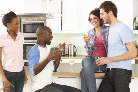 Group Of Young Friends Enjoying Glass Of Wine In Modern Kitchen photo