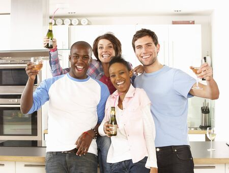 multi racial groups: Group Of Young Friends Enjoying Drink In Modern Kitchen Stock Photo