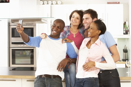 multi racial groups: Group Of Young Friends Taking Photo In Modern Kitchen Stock Photo