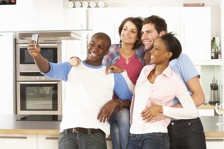 Groupe de jeunes amis prenant une Photo dans la cuisine moderne