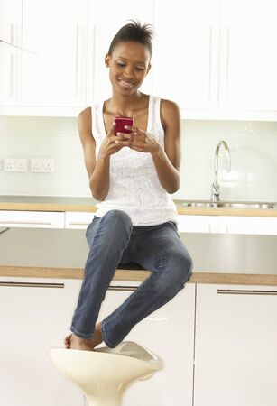 Woman Using Mobile Phone Sitting In Modern Kitchen photo