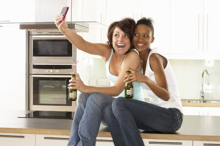Two Girlfriends Taking Photo With Digital Camera In Modern Kitchen photo