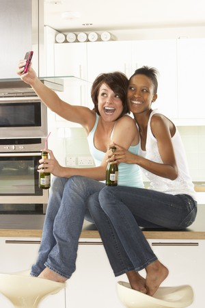 Two Girlfriends Taking Photo With Digital Camera In Modern Kitchen Stock Photo - 8452785