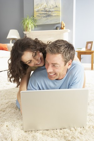 Couple Using Laptop Relaxing Laying On Rug At Home Stock Photo - 8452809