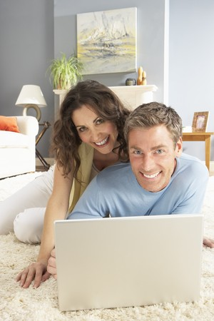 Couple Using Laptop Relaxing Laying On Rug At Home photo