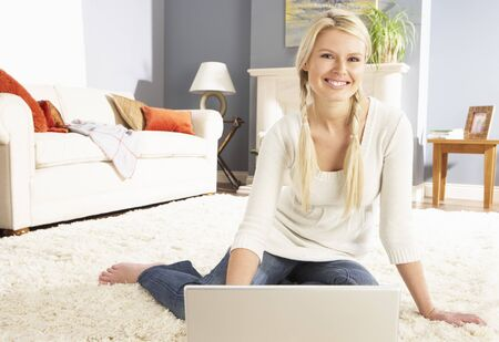 Woman Using Laptop Relaxing Sitting On Rug At Home Stock Photo - 8453023