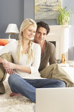 Couple Using Laptop Relaxing Sitting On Rug At Home Stock Photo - 8452718
