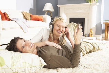 Couple Listening To MP3 Player On Headphones Relaxing Laying On Rug At Home photo