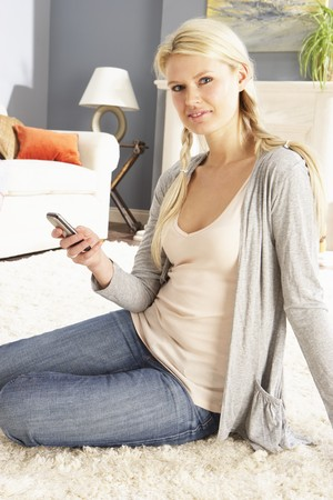 Woman Using Mobile Phone Relaxing Sitting On Rug At Home photo