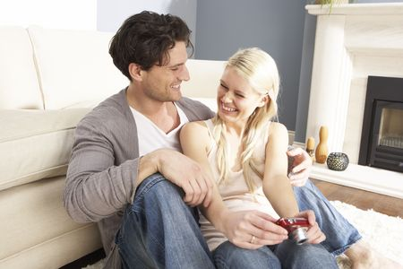 Couple Looking At Pictures On Digital Camera At Home photo