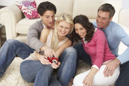 Group Of  Friends Looking At Pictures On Digital Camera At Home Stock Photo - 8452449