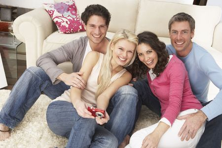 Group Of  Friends Looking At Pictures On Digital Camera At Home photo