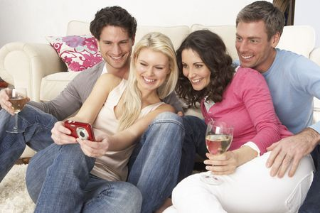 3 4 length: Group Of  Friends Looking At Pictures On Digital Camera At Home