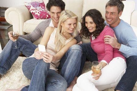 group picture: Grupo de amigos mirando fotograf�as en Smartphone en el hogar