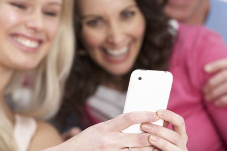 Two Girlfriends Looking At Pictures On Smartphone At Home photo