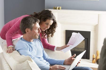 personal finance: Couple Using Laptop And Discussing Household Bills Sitting On Sofa At Home Stock Photo