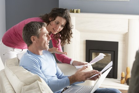Couple Using Laptop And Discussing Household Bills Sitting On Sofa At Home photo