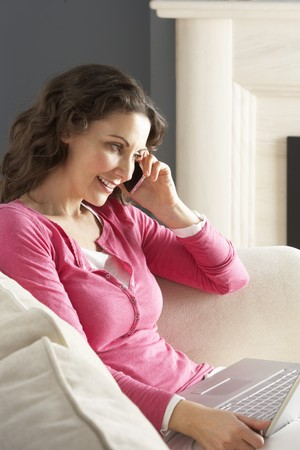 Woman Using Laptop Relaxing Sitting On Sofa At Home Talking On Phone photo