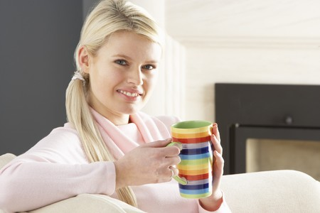 Woman Relaxing On Sofa At Home Drinking Cup Of Coffee photo