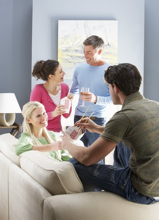Group Of  Friends Enjoying Chinese Takeaway Meal At Home photo