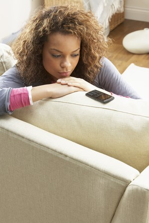 three women: Woman Sitting On Sofa Wating For Mobile Phone At Home