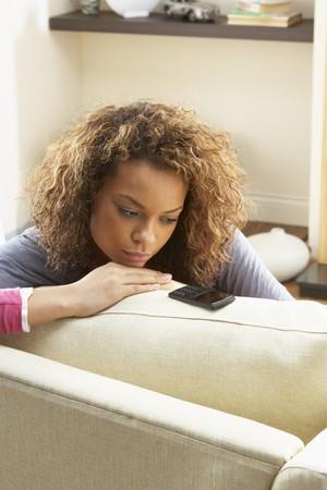 Femme assis sur le Sofa Wating pour t�l�phone mobile � la maison Banque d'images