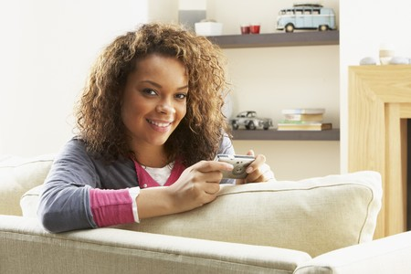 Woman Looking At Pictures On Digital Camera Relaxing Sitting On Sofa At Home photo