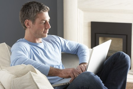 Man Using Laptop Relaxing Sitting On Sofa At Home Stock Photo - 8453275