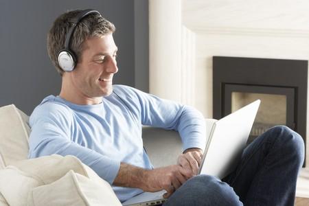 Man Using Laptop Wearing Headphones Relaxing Sitting On Sofa At Home photo