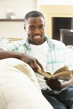 Young Man Relaxing Sitting On Sofa Reading Book At Home Stock Photo - 8453245