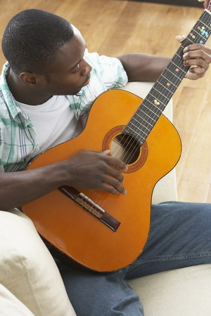 Young Man Relaxing Sitting On Sofa Playing Acoustic Guitar photo