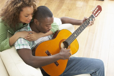 Young Couple Relaxing Sitting On Sofa Playing Acoustic Guitar photo