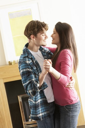 Romantic Young Couple Dancing Together In Living Room photo