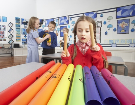 primary colours: Group Of Primary Schoolchildren Having Music Lesson In Classroom