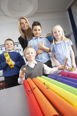grade schooler: Group Of Primary Schoolchildren And Teacher Having Music Lesson In Classroom Stock Photo
