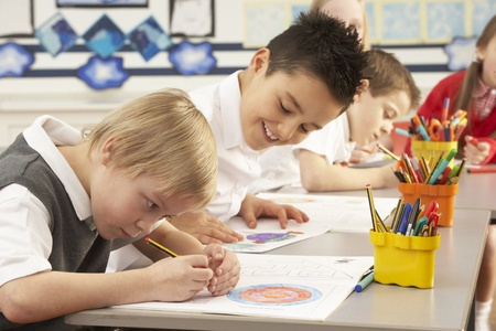 Group Of Primary Schoolchildren In Classroom Working At Desks photo