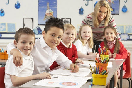 Group Of Primary Schoolchildren And Teacher Working At Desks In Classroom Stock Photo