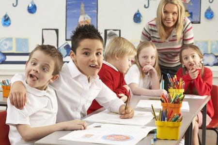 tutor: Grupo de escolares primarias y profesor funcionan a mesas en el aula